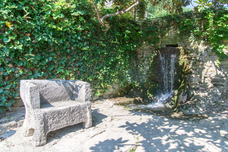 Stone chair next to waterfall