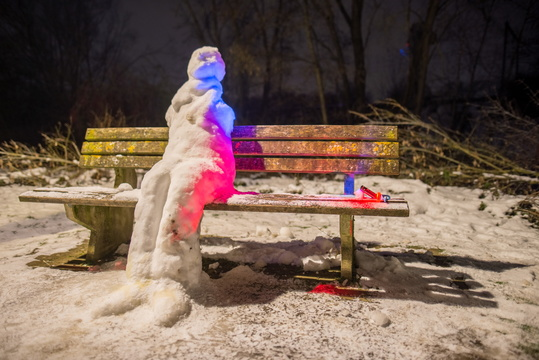 Snowman sitting on a bench